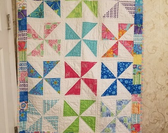 Bright pink, purple, aqua, green, yellow, orange and white pinwheel quilt