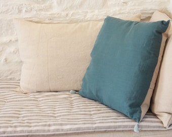 Teal linen cushion with blue PomPoms