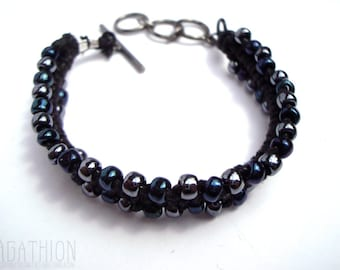 """Macrame Woven Beaded """"Zipper"""" style Bracelet with alternating iridescent and silver beads on black cotton cord with gunmetal toggle clasp"""