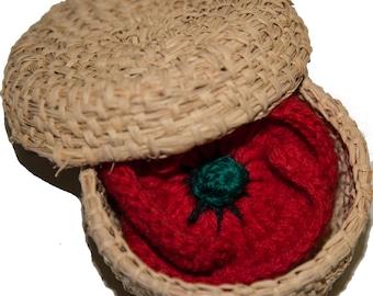 Crocheted poppy brooch in a hand-woven basket