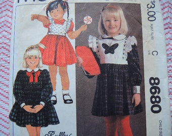 vintage 1980s simplicity sewing pattern 8680 toddler girls dress and detachable bib size 2