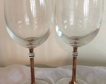 An elegant, vintage pair of gilded wine glasses.