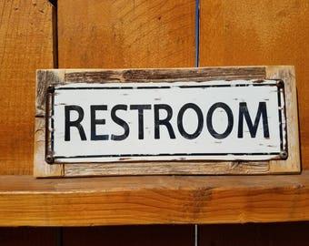 Restroom metal street sign on wood frame