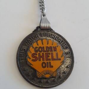 "Vintage 1930's advertising watch fob enamel badge ""This Watch Lubricated By Golden Shell Oil"" fantastic piece, measures 1 1/4 diameter"