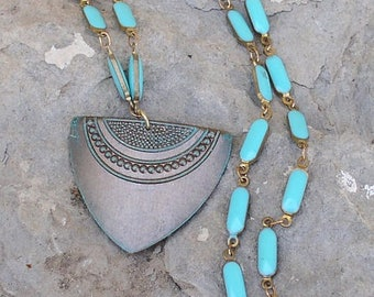 Brass shield pendant hangs on a long Turquoise colored brass chain