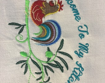 "A ""Welcome to my kitchen"" dish towel with a very colorful rooster."
