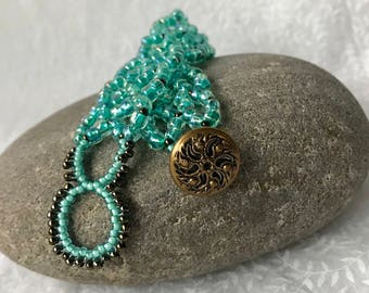 Beaded bracelet with right angle weave design in seafoam green beads with bronze colored bead accents. Vintage button clasp (#64).