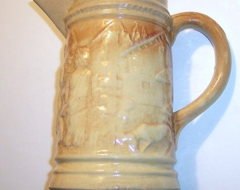 "Vintage Pitcher, Yellow with Sculpted figures, 10"" high, 6"" dia. at base"