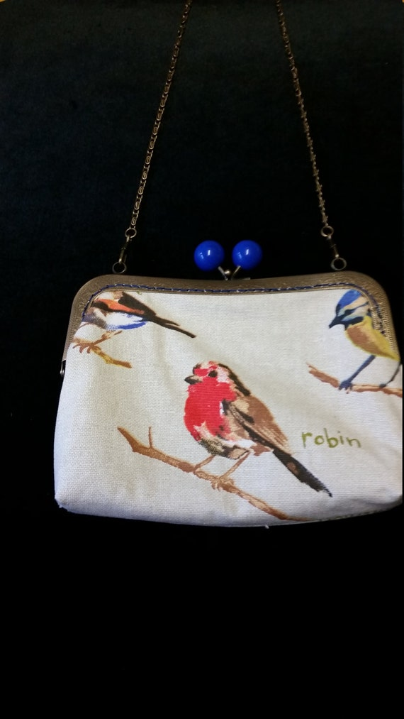 L449.  Small clutch bag with chain and bird design