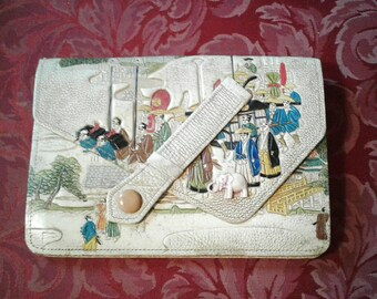 Amazing 1920s japanese cream and coloured tooled clutch with different scenes and figures snd a wonderful celluloid elephant on the front