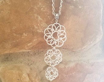 Graduated helm flower pendant on stainless steel chain.