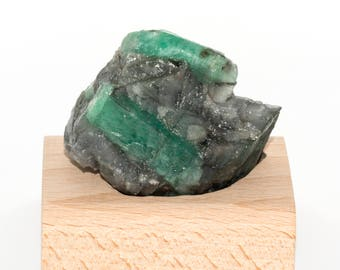 Rough emerald on base of beech wood of 113 grams.