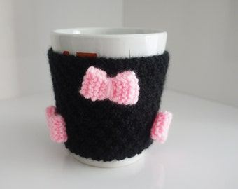 hand knitted black mug hug / cup cosy with pink bow and button detail