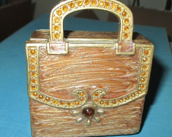 A unique handbag trinket box by partylite-a heavy metal decorated with topaz color jewels,with mirror and candle