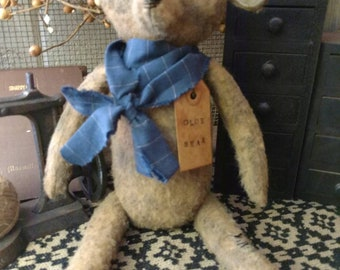 Carlyle, primitive teddy bear, wearing a blue homeapun tie and tag