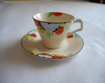 Art Deco cup and saucer orange and yellow black eyed Susans with larger blue cornflower. Gorgeous set. Made in England by Tunstall.