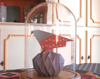 Origami birds on a nest under a glass dome