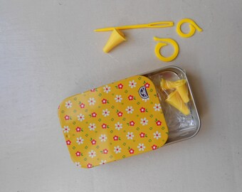 Yellow metal box containing the knitting accessories