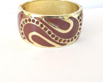 Gold tone metal hinge clamper bracelet, chocolate enamel, amber rhinestone