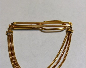 Vintage signed Swank gold tone cravat holder with a triple chain.