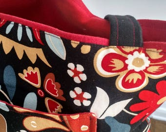 Multi-colored bag with black background and red interior. Black bottom on exterior with matching handles.
