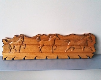 Rustic wooden coat rack for hanging on the wall, with carved horses, handmade