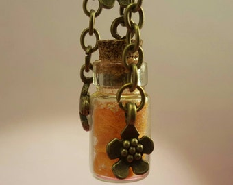 Glass vials with floral pendants on bronze chain