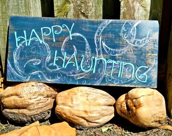Happy Haunting halloween beach sign on wood with octopus