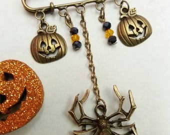 Halloween bronze kilt pin brooch featuring spider and pumpkin charms with bicone beads