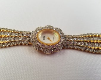 Vintage Bob Mackie gold tone watch with clear rhinestones.