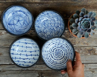 Set of 4 black stoneware dishes with white glaze inside ad blue patterns
