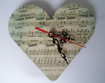 heart shaped wall clock with a printed old copy of sheet music on face