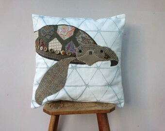 Turtle cushion cover appliqued using a variety of recycled fabrics.