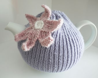 Knitted lilac tea cosy with pink flower decoration