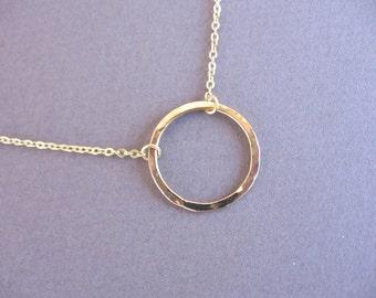 Hammered gold  hoop necklace.