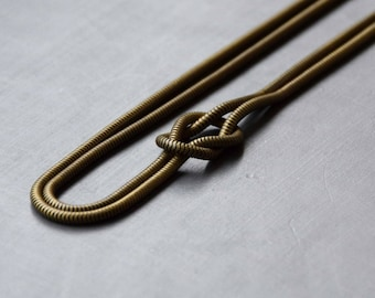 Bronze plated brass bow on a tubular chain necklace