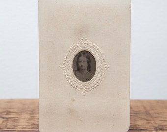 Antique Tintype of young girl in embossed paper frame.