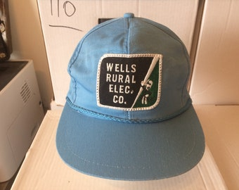 """Vintage Baseball Cap - """"Wells Rural Electric Co."""" (Wells, Nevada) - Reddy Kilowatt on patch - blue cap with black and green patch"""