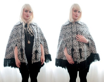 Vintage 1970s Guatemalan black white ethnic embroidered fringe poncho cape jacket pom-pom trim zip front bohemian hippie style cotton