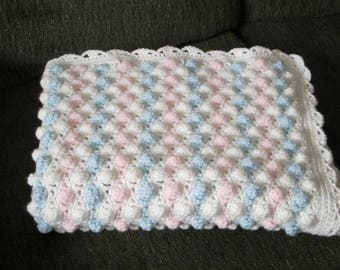 Baby blanket in pink, blue and white.