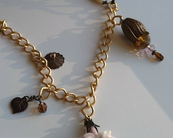 Long necklace with flower and charms brass