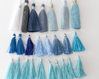 25 tassels - mostly blues and one white and one black - 2-3 inches in length