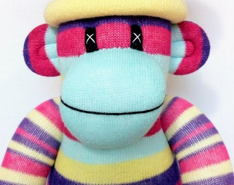 Fun Striped Sock Monkey with a  removable yellow pom pom hat