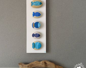5 pebbles painted blue fish on wooden stand