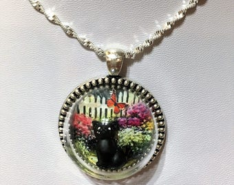 Black Cat in garden, white picket fence and flowers antique silver necklace glass globe