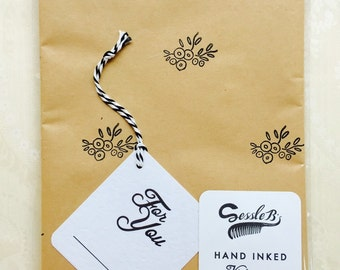 Retro hand stamped wrapping paper and gift tag. Vintage 1950's floral stamp. Black ink on brown paper.