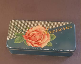 Vintage collectible accessories tin with pink rose.