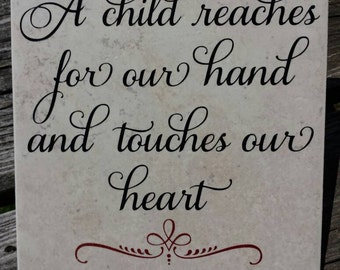 A child reaches for our hand and touches our heart decorative ceramic tile 6x6