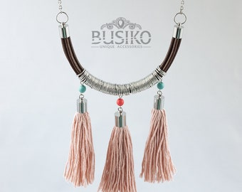 Tassel fringe necklace boho chic. Simple multi tassel jewelry hippie style. Leather cord pendant with coral pink tassels and silver rings.