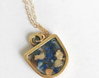 petit pendentif moderne en demi cercle rempli de paillettes de mica or et bleu lapis